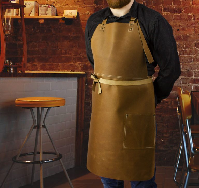 Long leather bib apron worn by model in bar