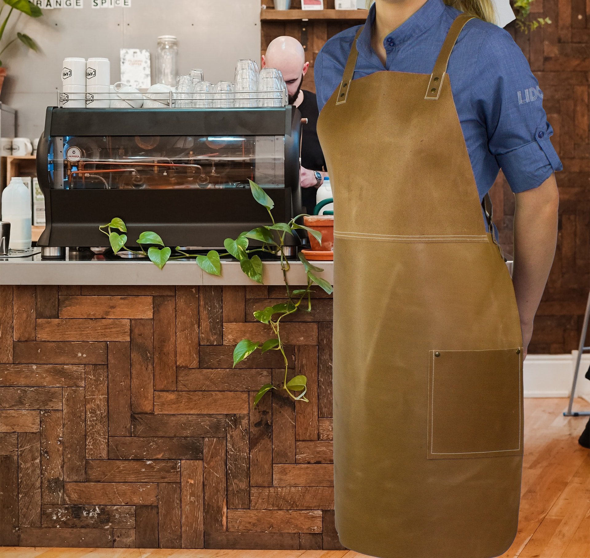 Cross back bib apron on model in cafe
